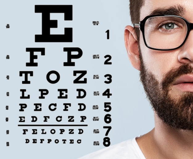 Half of male face and eye chart