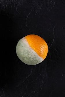 Половина заплесневелого апельсина на темном