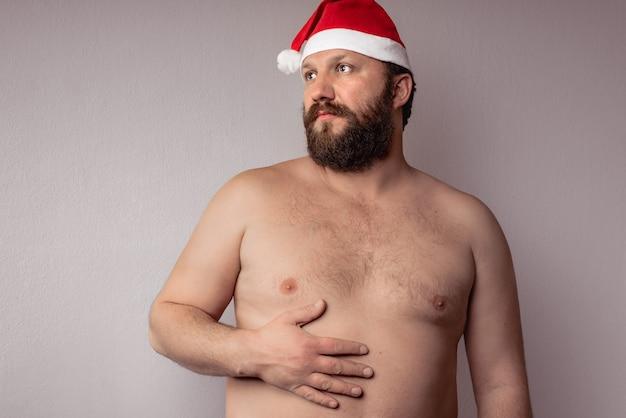 Half naked bearded man wearing a santa claus hat