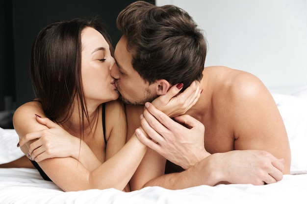 Half-naked couple man and woman hugging together, while lying in bed at home or hotel apartment