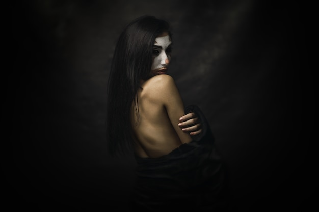 Half-naked female wearing clown makeup on her face standing in front of a black background