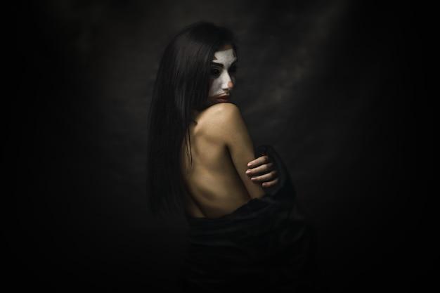 Donna seminuda che indossa il trucco da clown sul viso in piedi davanti a uno sfondo nero