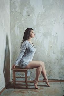 Half-naked girl posing alone sitting indoor