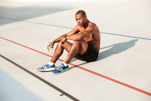 Полуголый молодой африканский спортсмен отдыхает