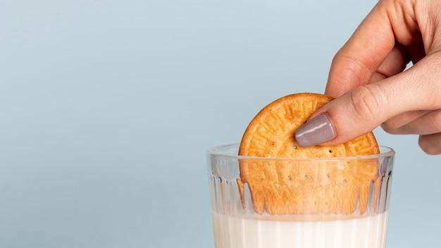 ミルクとコピースペースの背景のガラスに浸したビスケットの半分