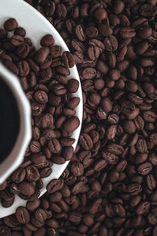 白で分離された新鮮な芳香の焙煎コーヒー豆の上に立っているホットブラックコーヒーのカップの半分