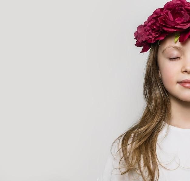 Половина лица маленькой девочки с закрытыми глазами и цветами на голове на светлом фоне