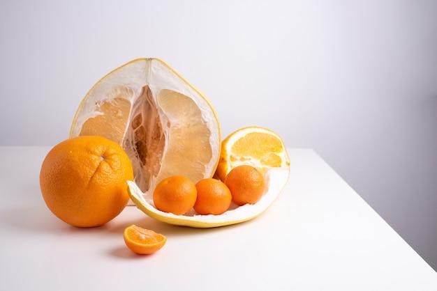 Половинка сочного свежего помело, апельсин, мандарины и цедра. цитрусовые на белом столе.