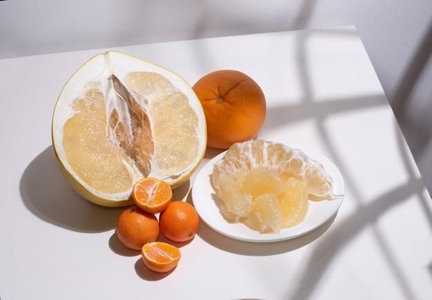 Половина свежего сочного помело, апельсина, мандаринов в солнечном свете с геометрическими тенями, крупным планом. цитрусовые на белом столе