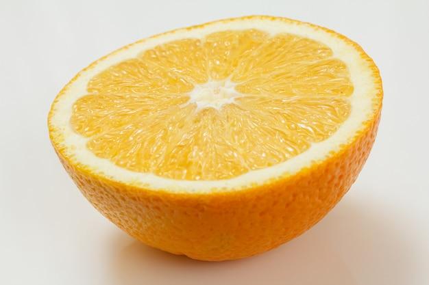 ジューシーなオレンジの半分が白い表面に横たわっています