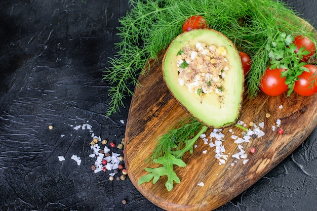 ケトジェニックアボカドの半分にマグロとソースが入っています。木製のまな板にトマトチェリー、ディル、ルッコラ。健康なケトン食。