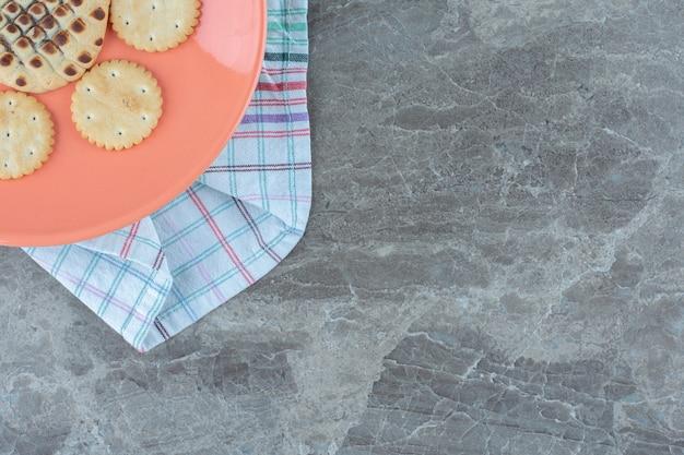 オレンジ色のプレートの半分の角度。プレート上の自家製クッキー。