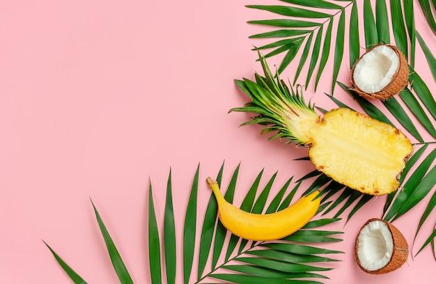 ピンクの背景にパイナップル、ココナッツ、バナナの半分とヤシの葉。コピースペース