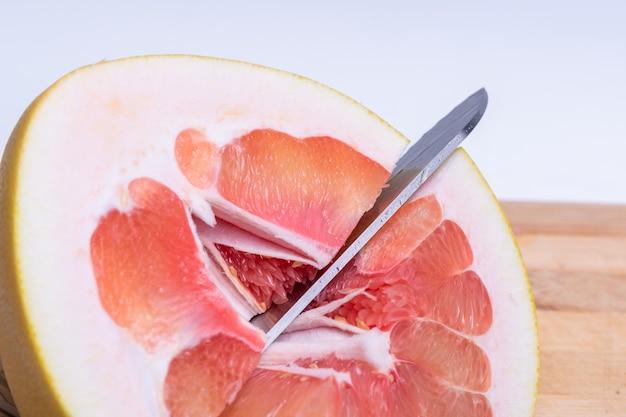 木製のまな板でカットされているザボンの柑橘系の果物の半分