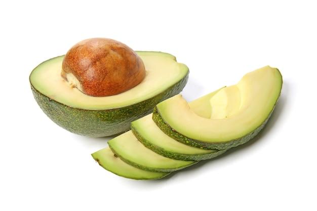 Половина спелого авокадо с ломтиками на белом