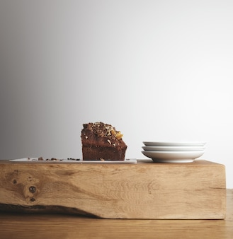 Половина вкусного шоколадного торта с сухофруктами на белой длинной тарелке рядом с тремя небольшими пустыми чайными тарелками на деревянном необработанном кирпиче и толстом столе в кафе-магазине