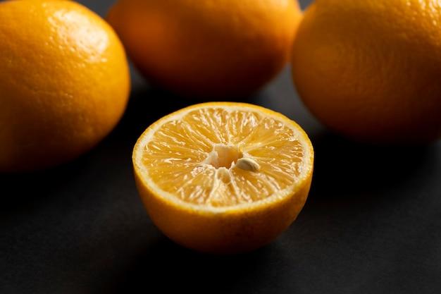 オレンジの半分は残りのオレンジの前にあります。黒いテーブルの上に熟したジューシーな黄色のオレンジ