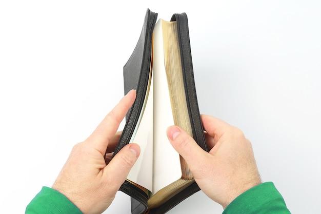 彼の手に半分開いた聖書。学問を通しての意味と教育