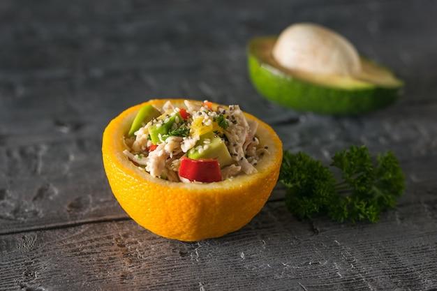 Половина апельсина с курицей и салатом из авокадо на фоне половинки авокадо. диетическое питание из тропических фруктов и курицы.