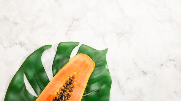 Half of papaya fruit on monstera leaf