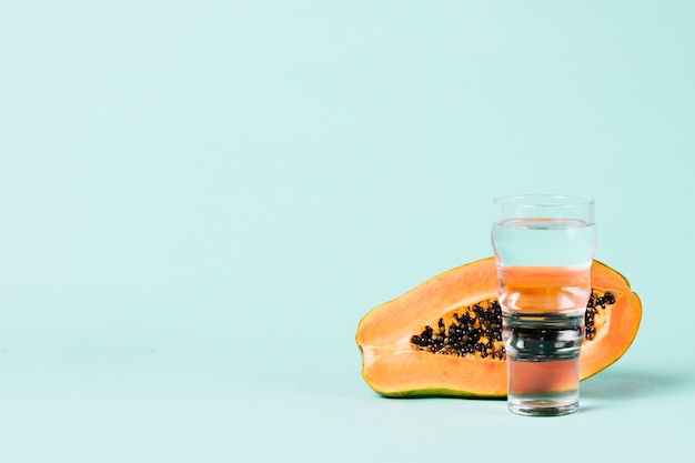 Half of papaya fruit and water glass