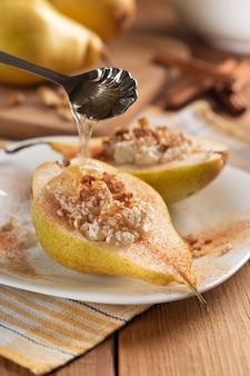 Половина груши с творогом, орехами, медом и корицей на белом блюде. поливают медом.