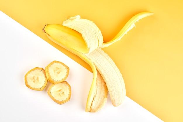 Половина очищенного банана и ломтики на желтом белом фоне с копией пространства