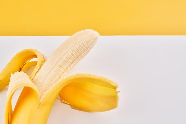 Половина очищенного банана на желтом белом фоне с копией пространства