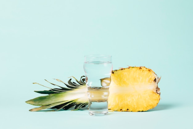 Half of pineapple with glass of water