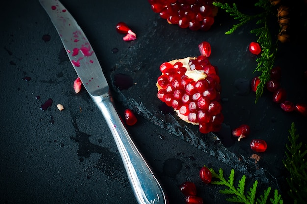 Half pomegranate and  seeds  a branch of spruce