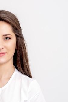 白い壁に若い女性のセラピストの半分の肖像画