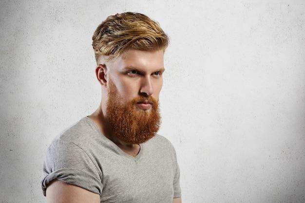 真面目な思慮深い顔の表情を持っている彼の前を見て、袖をまくった灰色のtシャツを着ているハーフプロファイルのハンサムな残忍なひげを生やした男。