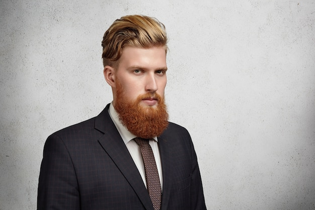 Mezzo profilo di un bel giovane banchiere barbuto in abito classico e cravatta che sembra serio e concentrato in piedi contro il muro grigio con copia spazio per il testo o il contenuto pubblicitario.