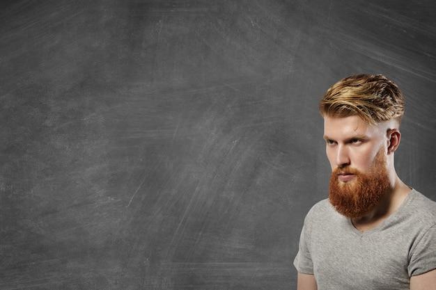 Colpo isolato di mezzo profilo di uomo barbuto serio che indossa una maglietta grigia con maniche rimboccate guardando davanti a lui con espressione preoccupata sul viso, pensando a qualcosa di importante