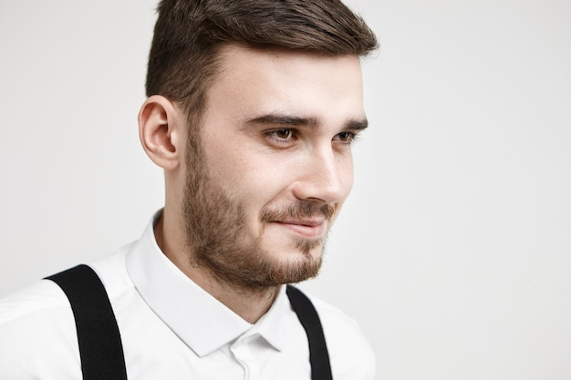 白いフォーマルなシャツを着てスタジオでポーズをとって、彼がいくつかの面白い話や冗談を思い出させるように思慮深く笑っている口ひげとあごひげを持つフレンドリーに見えるファッショナブルな若い男性の半分のプロフィール写真