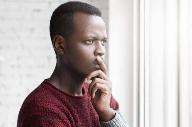 Half profile portrait of handsome young african american writer looking through window