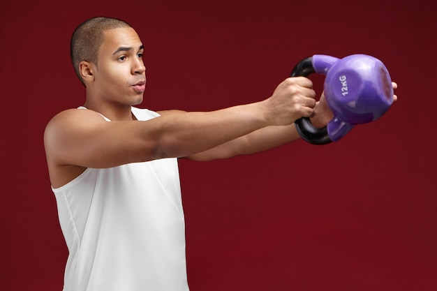 Half profile portrait of handsome young dark skinned bodybuilder with shaved head exercising with dumbbells. muscular african sportsman working out with heavy weight, building up arm muscles