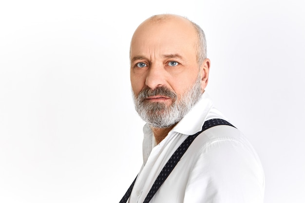 Half profile shot of handsome fashionable senior man with wrinkles, gray beard and blue eyes posing having serious facial expression looking at camera frowning eyebrows wearing elegant clothes