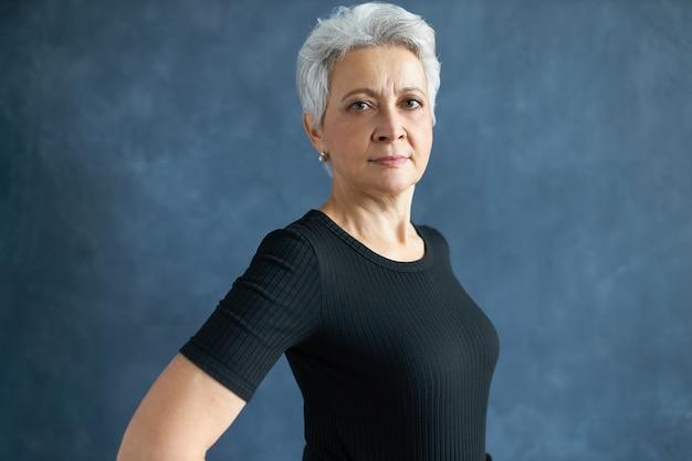 Mezzo colpo di studio profilo di pensionato donna europea dai capelli grigi in maglietta nera, fissando la telecamera con sguardo fiducioso, sorridente. posa femminile matura seria isolata.