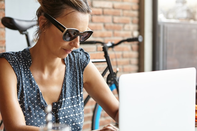 Half profile of stylish woman freelancer wearing sunglasses working remotely on modern laptop pc, having serious look