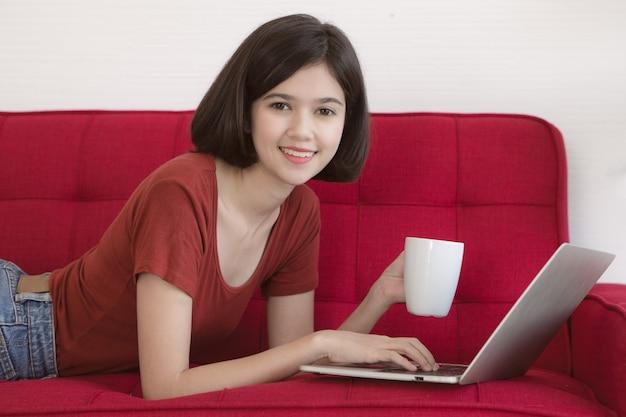 Тайско-немецкая милая девушка половинной расы, держащая белую кофейную чашку, лежащую на красном диване и использующая портативный компьютер, работает дома с чувством счастья.