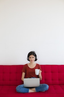 Half race thai-german cute girl wearing headphone holding white coffee cup sitting on red sofa with business graph and chart and using laptop notebook computer work from home with happiness feeling.