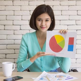 Тайско-немецкая милая девушка с короткими волосами на половинной гонке держит бумагу с бизнес-графиком и диаграммой, чтобы представить и показать на онлайн-конференции.