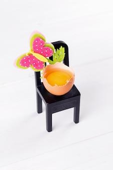 Половина сырого яйца с желтком сидит на черном стуле с украшением цветка пасхи. минимальная идея концепции пасхи, выборочный фокус
