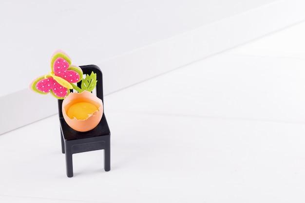 Половина сырого яйца с желтком сидит на черном стуле с украшением цветка пасхи. минимальная идея концепции пасхи