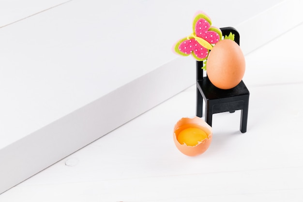 Половина сырое яйцо с желтком на белом столе и одно яйцо сидит на черном стуле с пасхальный цветок украшения. минимальная идея концепции пасхи, выборочный фокус