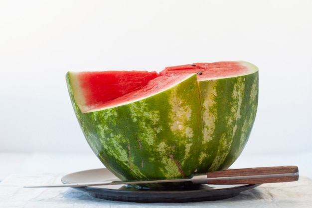 Half of red ripe watermelon on black plate on white background, there is large knife next to it