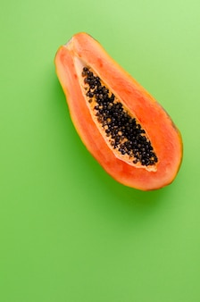 A half of ripe fresh papaya on green , exotic fruits concept
