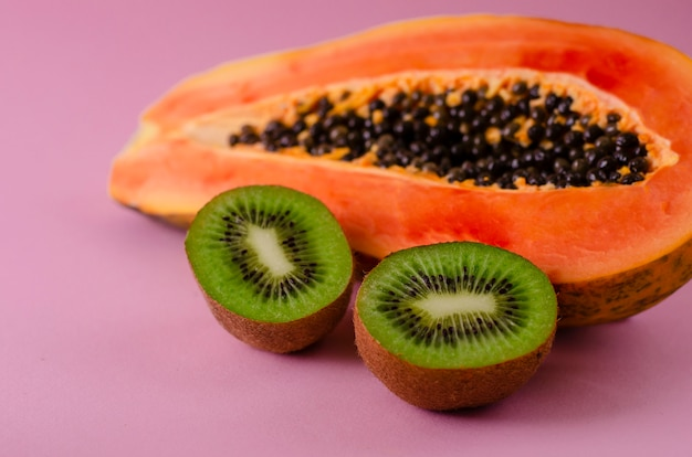 A half of ripe fresh papaya and kiwi on pink