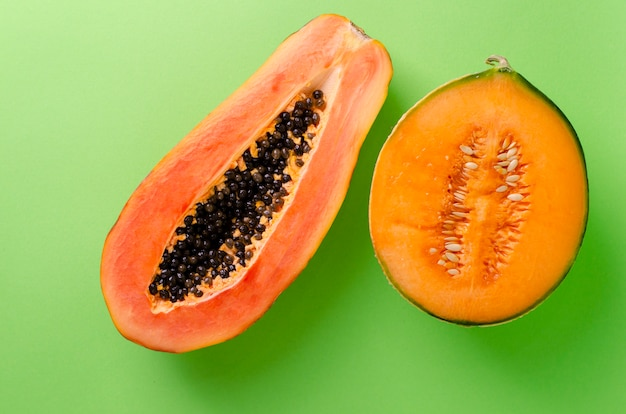 A half of ripe fresh papaya and melon on green